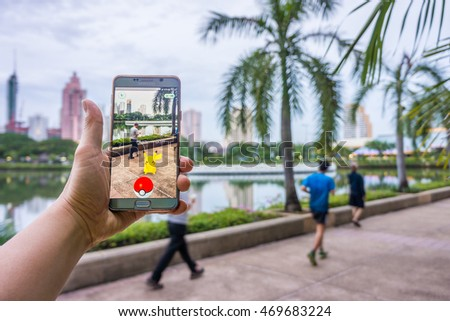 BANGKOK - AUGUST 10, 2016: Enthusiastic Pokemon player is jogging and catching Pikachu in the street of Benchakiti Park. The Pokemon Go has started craze in Thailand since August 6, 2016.