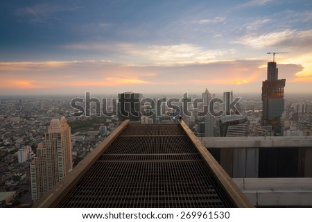 Bangkok city sunset view from rooftop of skyscraper building with steel grate floor  - stock photo