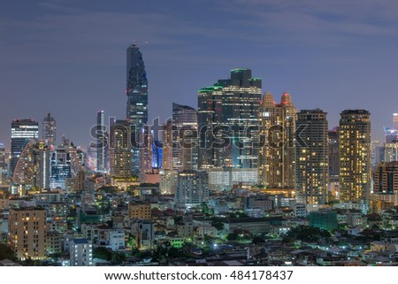 Bangkok Cityscape at night. Multiple tall buildings and glowing lights.