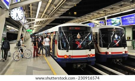 BANGKOK - DEC 5: Passengers board a BTS Skytrain at a city centre station on Dec 5, 2011 in Bangkok Thailand. The Thai capital's BTS rail public transport system serves 600,000 passengers daily. - stock photo