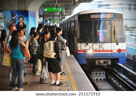 BANGKOK - DEC 22: Passengers wait for an approaching train on a platform at a city centre BTS station on Dec 22, 2010 in Bangkok, Thailand. The BTS has a daily ridership of 600,000 passengers.  - stock photo