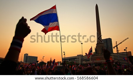 BANGKOK-DEC 22: Thai flag and hands raising against twilight sky at Victory monument on December 22, 2013 in Bangkok, Thailand. About 6 million Thai protesters gather in many Bangkok areas today. - stock photo