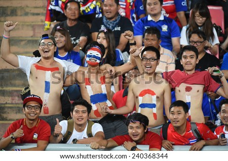 BANGKOK, DEC 17:Unidentified Thai fans cheer in action during the competition 2014 AFF Suzuki Cup between Thailand and Malaysia at Rajamangala stadium on December 17, 2014 in Bangkok, Thailand.  - stock photo