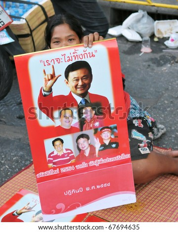 BANGKOK - DECEMBER 19: A Red Shirt at a protest at Rachaprasong displays an image of Thaksin Shinawatra, former PM of Thailand who was ousted in a 2006 coup on December 19, 2010 in Bangkok, Thailand. - stock photo