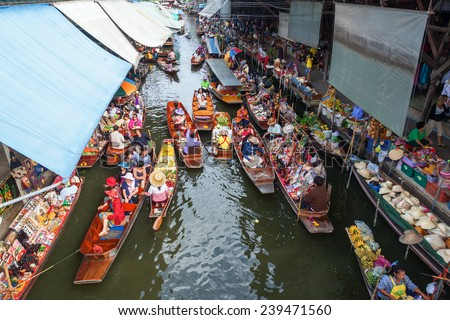 BANGKOK-DECEMBER 13: floating market Damnoen Saduak with unidentified people on December 13, 2014 in Bangkok, Thailand. The market that is a great tourist attraction is located on a Khlong in Thailand - stock photo