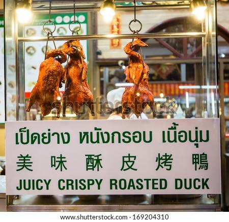 BANGKOK- DECEMBER 31: Thai people sell food by the Yaowarat road (menu roast duck) on DEC 31, 2013 in Bangkok, Thailand.  - stock photo