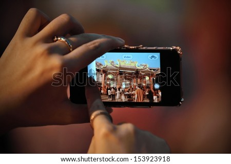 BANGKOK - FEB 9: A temple-goer uses a smartphone to capture Chinese new year celebrations in Bangkok's chinatown district on Feb 9, 2013 in Bangkok, Thailand.   - stock photo