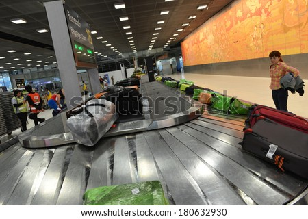 BANGKOK - FEB 20: Unidentified travellers wait at baggage reclaim at Suvarnabhumi International Airport on Feb 20, 2014 in Bangkok, Thailand. The airport handles 45 million passengers annually 2014. - stock photo