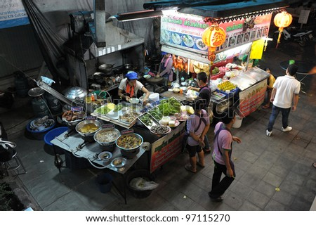 BANGKOK - FEB 12: Unidentified vendors prepare food at a street side restaurant on Feb 12, 2012 in Bangkok, Thailand. Government figures indicate about 16,000 registered street vendors in Bangkok. - stock photo