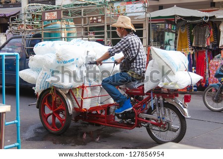 BANGKOK  FEBRUARY 29. A man overloaded with ice bags on scooter on February 29, 2012 in Bangkok, Thailand. Huge quantites of ice are used everday. - stock photo