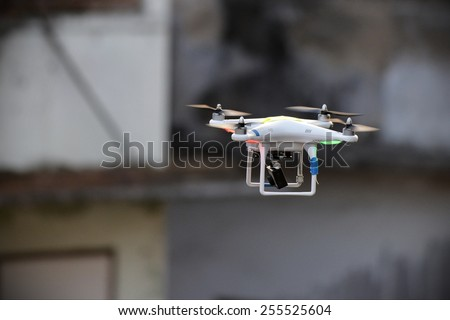 BANGKOK - JAN 17: A drone fitted with a camera flies above a political rally on Jan 17, 2014 in Bangkok, Thailand. There is currently no legislation regulating the use of drones in Thailand. - stock photo