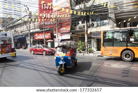 BANGKOK - JAN 24: A three wheeled tuk tuk taxi on a street in the Thai capital on Jan 24, 2014 in Bangkok, Thailand. Tuk tuks are commonly used in transporting people and goods around the capital.