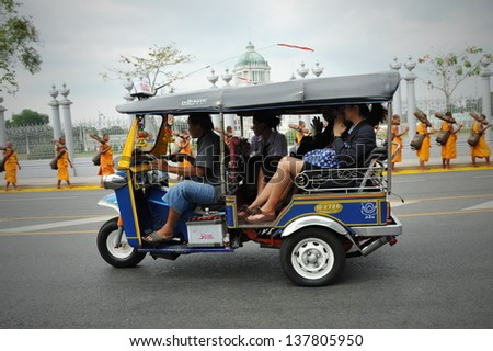 BANGKOK - JAN 25: A tuk tuk taxi transports passengers on a road in Dusit district on Jan 25, 2013 in Bangkok, Thailand. Tuk tuks can be hired from as little as $1 or B30 a fare for shop trips. - stock photo