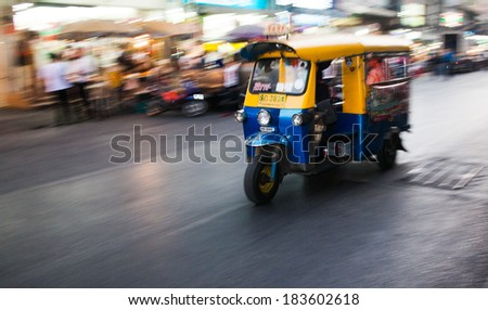 BANGKOK - JAN 24: A tuk tuk taxi transports passengers  on Jan 24, 2014 in Bangkok, Thailand. Tuk tuks can be hired from as little as $1 or B30 a fare for shop trips. - stock photo