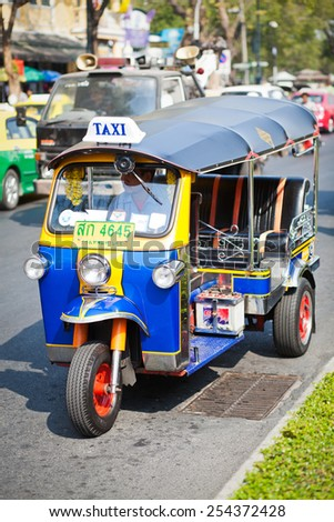 BANGKOK - JAN 24: A tuk tuk taxi transports passengers on Jan 24, 2014 in Bangkok, Thailand. Tuk tuks can be hired from as little as $1 or B30 a fare for shop trips - stock photo