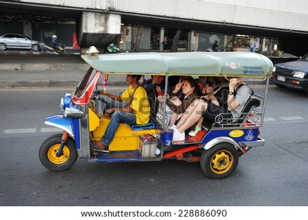 BANGKOK - JAN 14: An overcrowded tuk tuk taxi transports passengers on a city centre a road on Jan 14, 2013 in Bangkok, Thailand. Tuk tuks can be hired from $1 or B30 a fare for shop trips. - stock photo