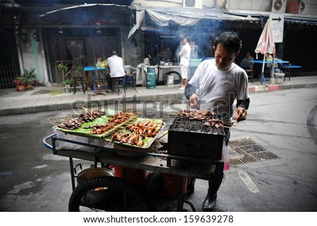 BANGKOK - JAN 27: An unidentified street vendor cooks at a roadside restaurant on Jan 27, 2012 in Bangkok, Thailand. From government stats there are over 16,000 registered street vendors in Bangkok. - stock photo