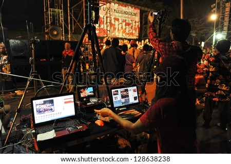 BANGKOK - JAN 29: An unidentified video editor operates an editing system during a large red-shirt rally on the Royal Plaza on Jan 29, 2013 in Bangkok, Thailand. - stock photo