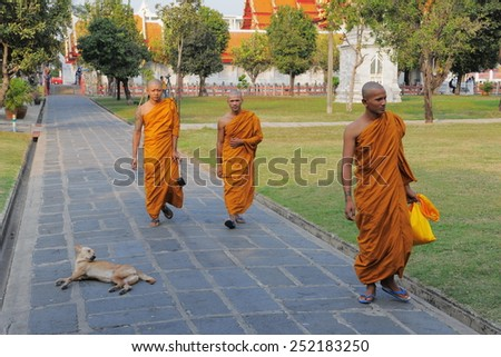 BANGKOK - JAN 20: Buddhist monks walk through the grounds of a city centre temple on Jan 20, 2011 in Bangkok, Thailand. There are an estimated 460,000 ordained monks in the Kingdom of Thailand. - stock photo