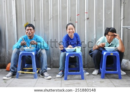 BANGKOK - JAN 13: Construction workers dine at a street-side restaurant on Jan 13, 2011 in Bangkok, Thailand. The Thai capital is undergoing a property boom with numerous construction projects. - stock photo