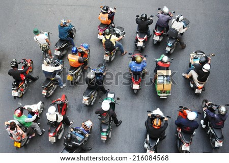 BANGKOK - JAN 13: Motorcyclists stop at a city centre junction during rush hour on Jan 13, 2011 in Bangkok, Thailand. Motorcycles are often the transport of choice for Thai capital's congested roads. - stock photo