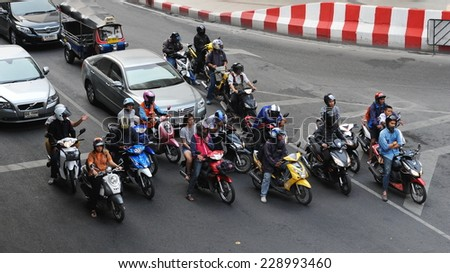 BANGKOK - JAN 23: Motorcyclists wait at a junction during rush hour on Jan 23, 2013 in Bangkok, Thailand. Motorcycles are often the transport of choice on Bangkok's heavily congested roads. - stock photo
