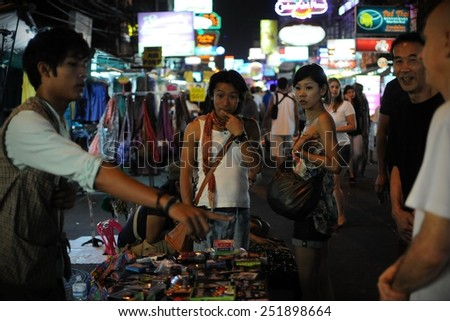 BANGKOK - JAN 4: Tourists watch a magic show on Khao San Road on Jan 4, 2011 in Bangkok, Thailand. Khao San is popular with backpackers for its nightlife and affordable accommodation. - stock photo