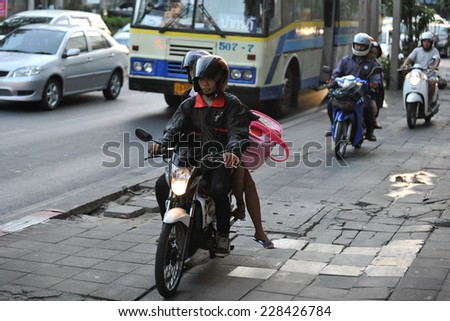 BANGKOK - JAN 10: Unidentified motorcyclists ride on a pavement during rush hour on Jan 10, 2013 in Bangkok, Thailand. Road traffic laws are often poorly enforced and overlooked in Thailand. - stock photo