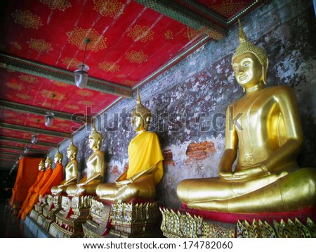 BANGKOK-JANUARY 4: Golden Buddha statues in a row inside the temple hall of Wat Suthat on January 4, 2012 in Bangkok, Thailand. Wat Suthat is a famous temple built during 17th century by King Narai.
