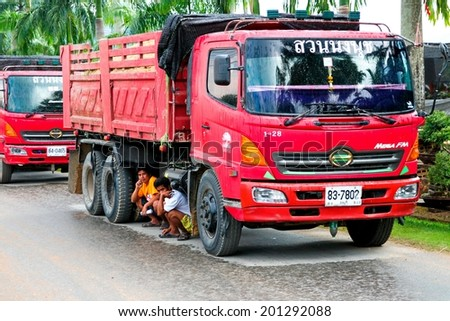 BANGKOK - JANUARY 10 : Men workers under a truck outwaits rain in the road on January 10, 2013 in Bangkok, Thailand. - stock photo