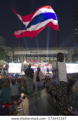 BANGKOK - JANUARY 21 : Protester applauds with Thai flag in an anti-government rally at  Pathumwan junction on January 21, 2014 in Bangkok Thailand.
