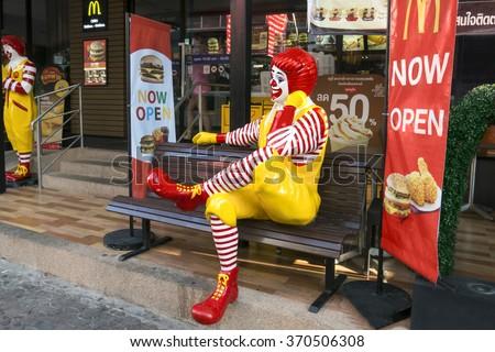 BANGKOK - JANUARY 02, 2016: Ronald McDonald character sitting on bench at McDonald Restaurant in Bangkok, Thailand. McDonald's Corporation is the world's largest burger fastfood restaurants. - stock photo