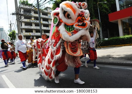 BANGKOK - JUL 21: A lion dance troupe performs on a street on Jul 21 2012 in Bangkok, Thailand. Some Chinese temples in the Thai capital raise funds by sending dance troupes to visit local businesses.