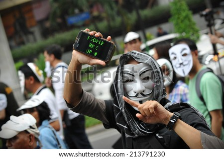 BANGKOK - JUN 16: A masked protesters joins an anti government protest on a city centre street on Jun 16, 2013 in Bangkok, Thailand. Many protesters wore the anonymous or Guy Fawkes mask.  - stock photo