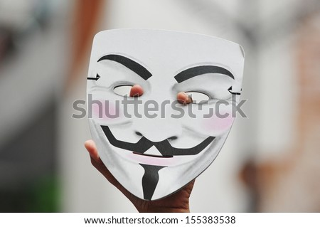 BANGKOK - JUN 30: A protester holds up a Guy Fawkes mask during an anti-government rally on Jun 30, 2013 in Bangkok, Thailand. Protesters known as V for Thailand call for the government to be removed. - stock photo