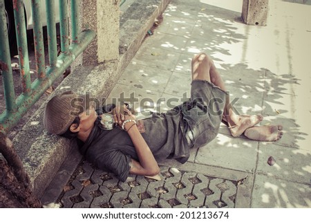 BANGKOK - Jun 27: An unidentified man sleeps on the street in city centre on Jun 27, 2014 in Bangkok, Thailand. The government estimates 4,000 homeless in Bangkok while NGOs put the figure far higher