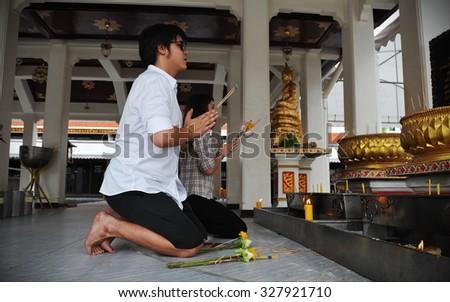 BANGKOK - JUN 5: Buddhist devotees make merit at the City Pillar Shrine on Jun 5, 2013 in Bangkok, Thailand.  - stock photo