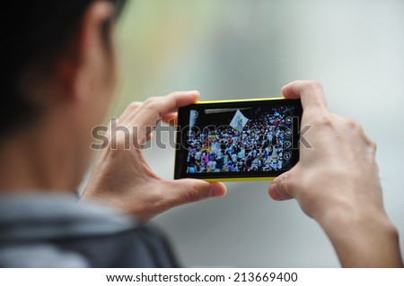 BANGKOK - JUNE 30: A passerby uses a smartphone to capture an anti government rally on June 30, 2013 in Bangkok, Thailand. The protesters call for political reform and the government to be overthrown. - stock photo