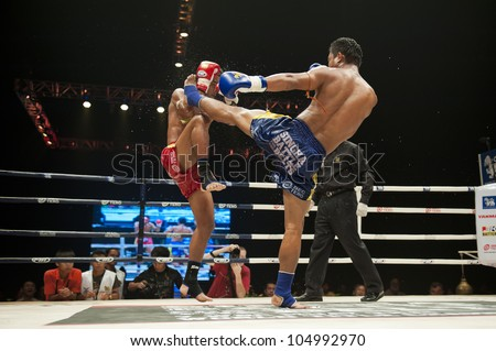 """BANGKOK - JUNE 9: Muay Thai fight - two unidentified thai kickboxer at """"BATTLE FOR THE BELTS"""" event on June 9, 2012 in Bangkok, Thailand - stock photo"""