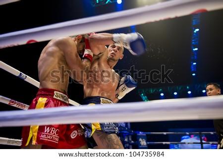 "BANGKOK - JUNE 9: Muay Thai Super Welterweight World Championship - Joe Schilling (USA) strikes Karapet Karapetyan (NL) with his elbow at ""BATTLE FOR THE BELTS"" on June 9, 2012 in Bangkok, Thailand - stock photo"