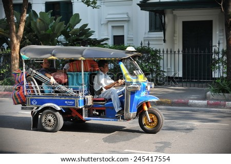 BANGKOK - MAR 19: A tuk tuk taxi ferries a passenger along a city centre street on Mar 19, 2013 in Bangkok, Thailand. Tuk tuks can be hired from as little as $1 per trip.  - stock photo