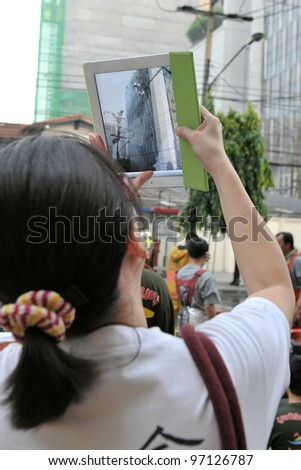 BANGKOK - MAR 5: An unidentified passer by uses a tablet computer to photograph firefighters tackling a blaze at Fico Building on Asoke Road in the city centre on Mar 5, 2012 in Bangkok, Thailand. - stock photo
