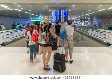 BANGKOK - MAR 01: An unidentified travellers view a departures board at Suvarnabhumi International Airport on March 01, 2015 in Bangkok, Thailand. The airport handles 45 million passengers annually.  - stock photo