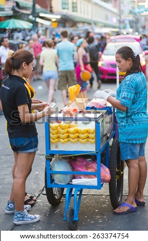 BANGKOK - MARCH 10, 2015: An unidentified woman sells cut fruit in Khao San Road. It is the heart of the tourist area with plenty of budget hotels and guesthouses. - stock photo