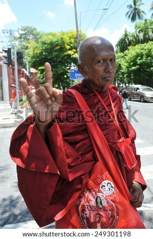 BANGKOK - MAY 8: A Buddhist monk Red Shirt supporter gestures while attending a rally at the Thai Parliament on May 8, 2013 in Bangkok, Thailand. Protesters rallied against alleged judicial bias. - stock photo