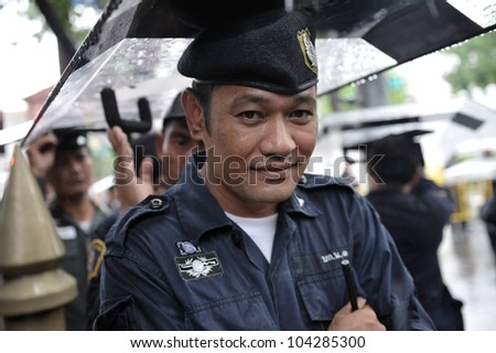 BANGKOK - MAY 31: A policeman uses a riot shield to shelter from rain during People's Alliance for Democracy, or yellow-shirt, rally outside Parliament on May 31, 2012 in Bangkok, Thailand. - stock photo