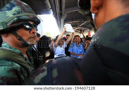 BANGKOK - MAY 24: A small group of unidentified people holding banners during a rally to condemn the Military coup on May 24, 2014 in Bangkok, Thailand. - stock photo