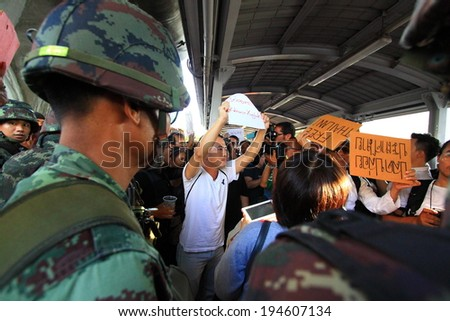 BANGKOK - MAY 24: A small group of unidentified people holding banners during a rally to condemn the Military coup on May 24, 2014 in Bangkok, Thailand.