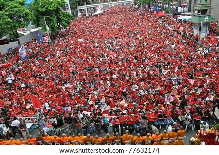BANGKOK - MAY 19: 20,000 red-shirts protest at Ratchaprasong on May 19, 2011 in Bangkok, Thailand. The red-shirts gathered to mark one year since 91 people died in protests in the Thai capital. - stock photo