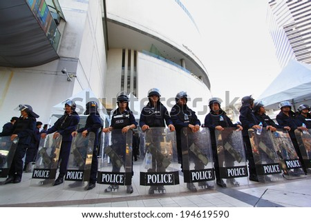 BANGKOK - MAY 24: Riot police stand guard on Bangkok art and culture centre during a violent anti-Military coup on May 24, 2014 in Bangkok, Thailand. - stock photo